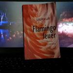 """Das Buch """"Flamingofeuer"""" steht auf einer Laptop-Tastatur. Es lehnt am Laptop-Bildschirm auf dem man ein Foto von Flamingos im Kölner Zoo sieht."""