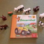 """Das Buch """"Frag doch mal die Maus - Bauernhof"""" auf einem Teppich liegend, umringt von Lego Duplo Tieren"""