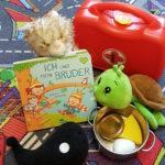"""Das Bilderbuch """"Ich und mein Bruder"""" liegt auf einem Spieleteppich. Es lehnt an einer Stoffkatze. Ein Spielzeugarztkoffer steht im Hintergrund. Davor krabbelt eine Stoffschildkröte über einen Spielzeugkochtopf. Im Vordergrund liegt ein Stoff-Wal (das Maskotchen des Magellan-Verlags)"""