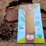 """Das Bilderbuch """"So hoch der Baum"""" vor einer alten Backsteinmauer"""